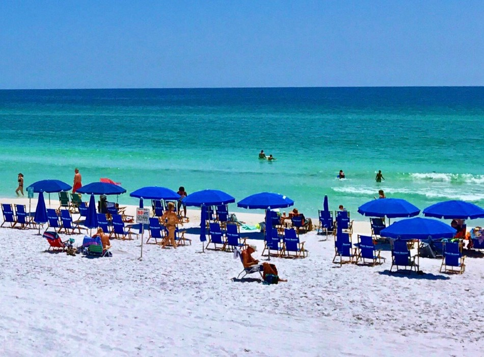 June White Decker Beach with colored umbrellas on white sand overlooking emerald green water