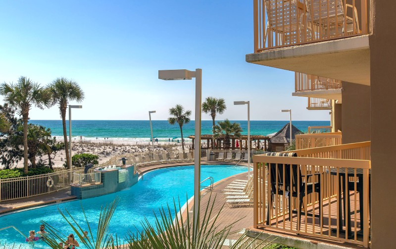 Hotel swimming pool with palm trees located on the beach in Destin